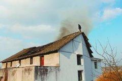 老人与老伴吵架 站在失火屋顶跳楼被消防拉回